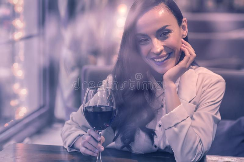 Donna piacevole allegra che beve vino rosso da solo fotografia stock