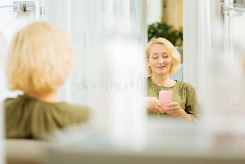 Donna piacevole allegra che per mezzo del suo aggeggio fotografie stock