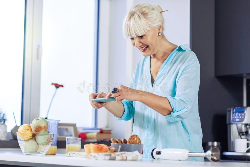 Donna piacevole allegra che prende le immagini di alimento fotografia stock