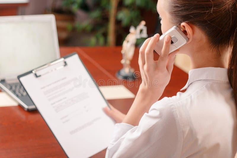 Donna piacevole che parla sul telefono sul lavoro fotografia stock