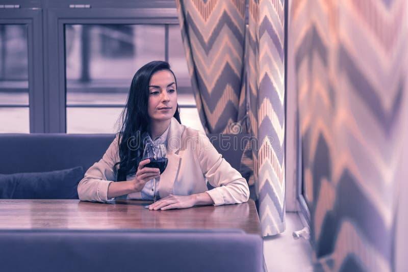 Donna piacevole piacevole che si siede alla tavola del ristorante immagini stock
