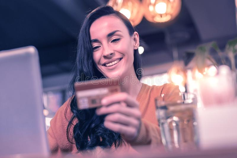 Donna piacevole contentissima che esamina la sua carta di credito fotografie stock libere da diritti