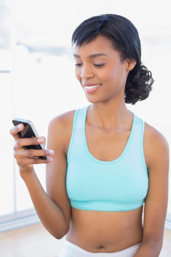 Donna piacevole di misura che manda un sms con il suo telefono cellulare immagini stock