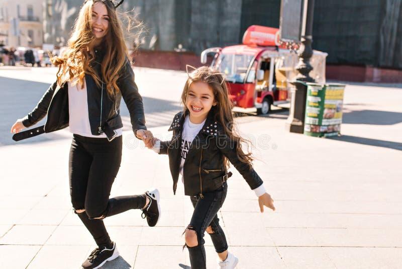 Donna piacevole in pantaloni e scarpe da tennis neri che spende tempo con la figlia che corre attraverso la città con il bus ross fotografia stock