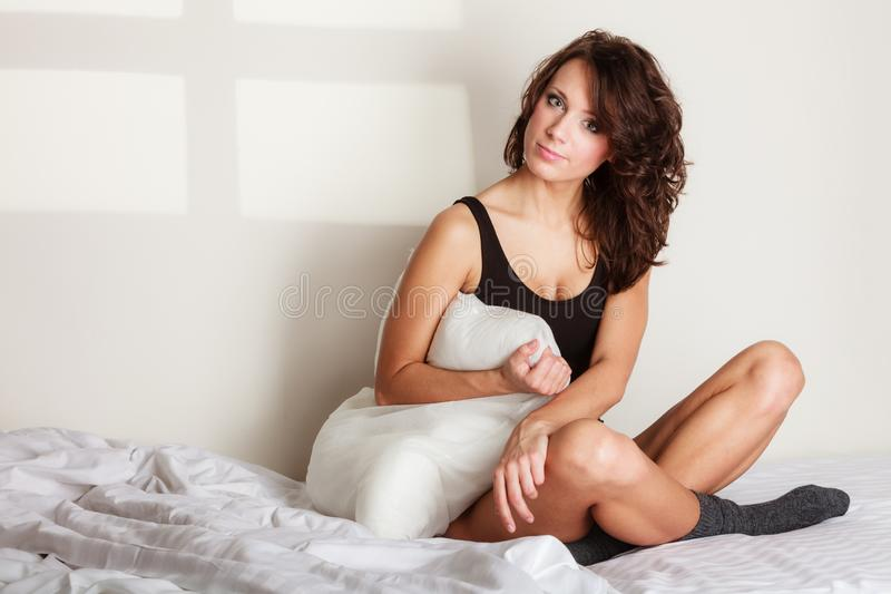 donna pigra della ragazza con il cuscino sul letto in camera da letto fotografie stock