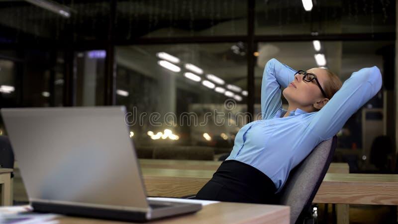 Donna pigra di affari che pende indietro sulla sedia invece del funzionamento, rilassamento fotografia stock libera da diritti
