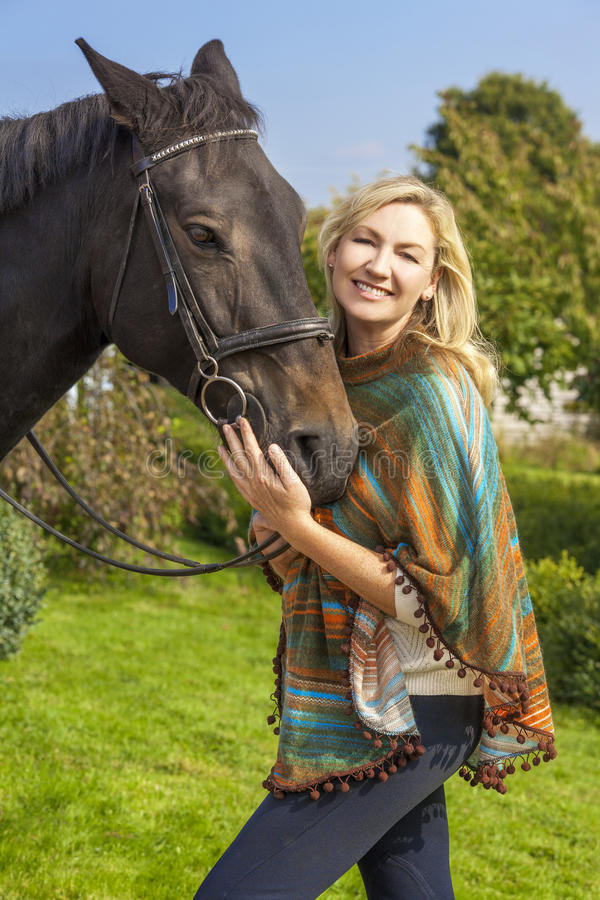 Donna in Poncho Leading Her Horse immagini stock