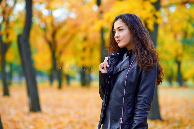 Donna in posa con foglie autunnali nel parco cittadino, ritratto all'aperto fotografia stock