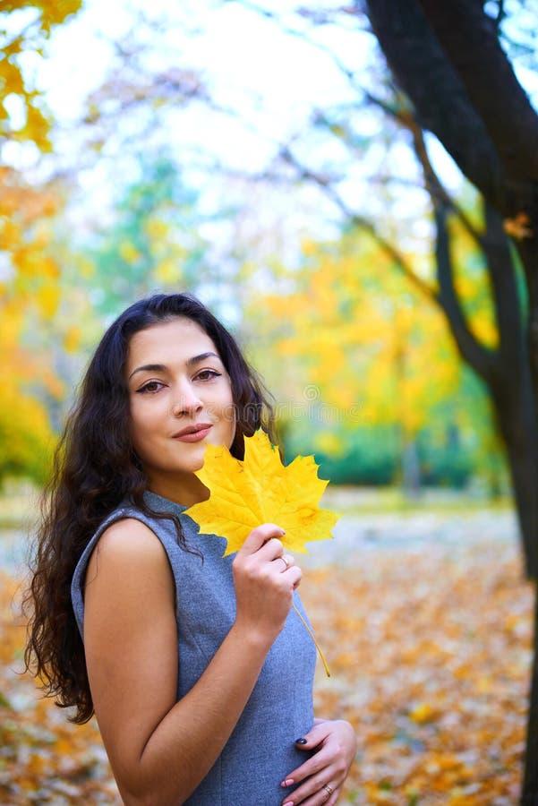 Donna in posa con foglie autunnali nel parco cittadino, ritratto all'aperto fotografie stock libere da diritti
