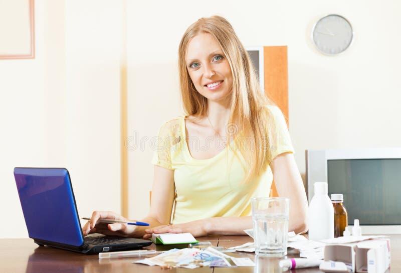 Donna positiva che legge sulle medicine su Internet fotografia stock libera da diritti