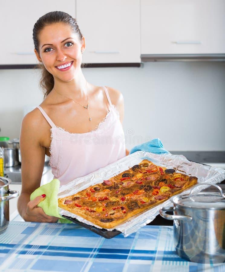 Donna positiva che produce pizza fotografia stock libera da diritti