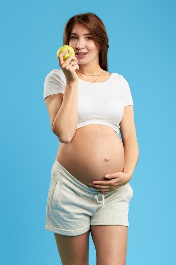 Donna positiva con capelli marroni lunghi che tengono una mela e che toccano la sua grande pancia fotografia stock