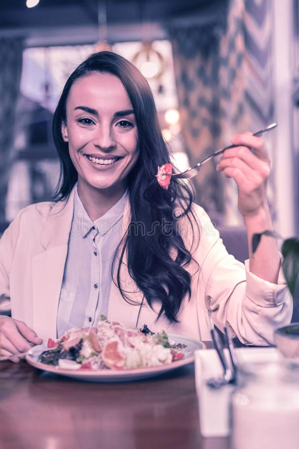 Donna positiva contentissima che mangia macedonia saporita fotografia stock