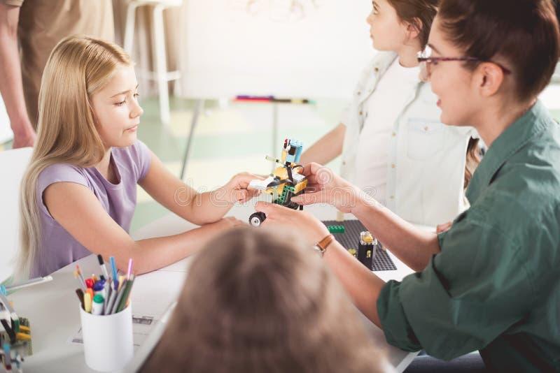 Donna positiva e bambini che creano robot immagini stock