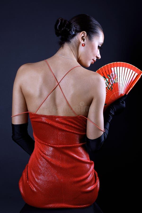 Donna posteriore del latino con il ventilatore rosso immagini stock libere da diritti