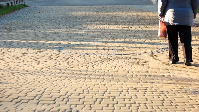 Donna posteriore di vista che cammina sui ciottoli immagini stock libere da diritti