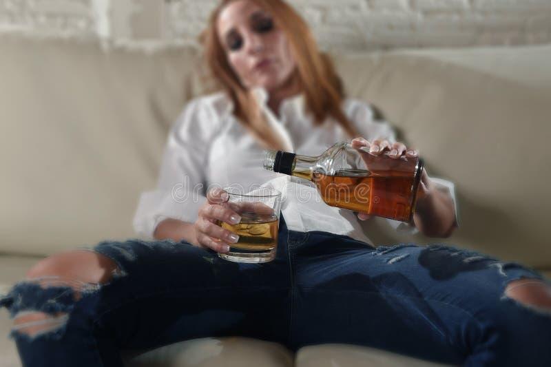 Donna potabile alcoolizzato depresso triste che beve a casa nell'abuso di alcool e nell'alcolismo della casalinga fotografie stock
