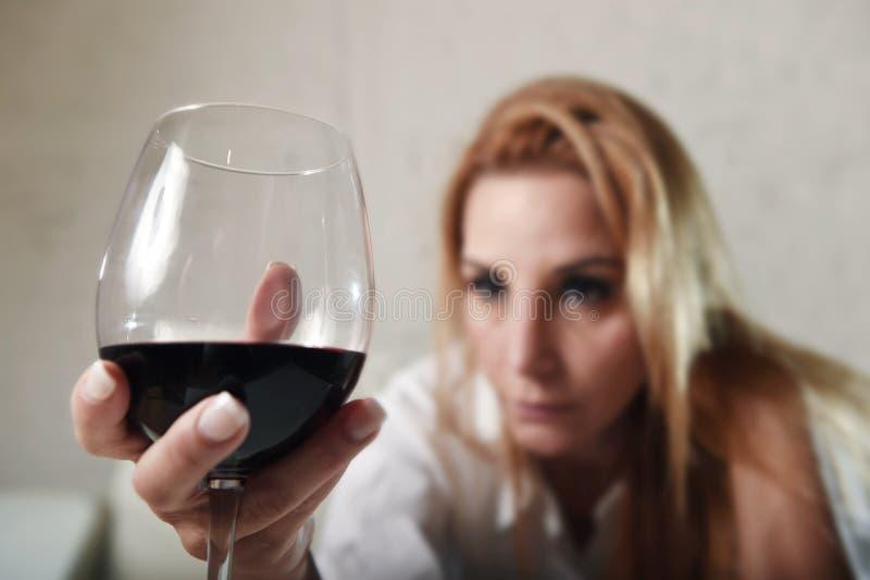 Donna potabile alcoolizzato depresso triste che beve a casa nell'abuso di alcool e nell'alcolismo della casalinga immagini stock libere da diritti