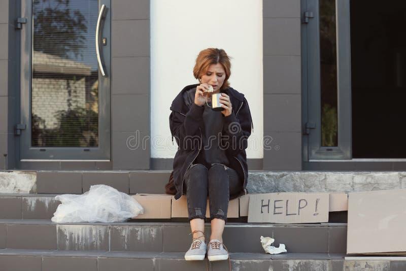Donna povera con il pezzo di pane e di tazza fotografia stock libera da diritti
