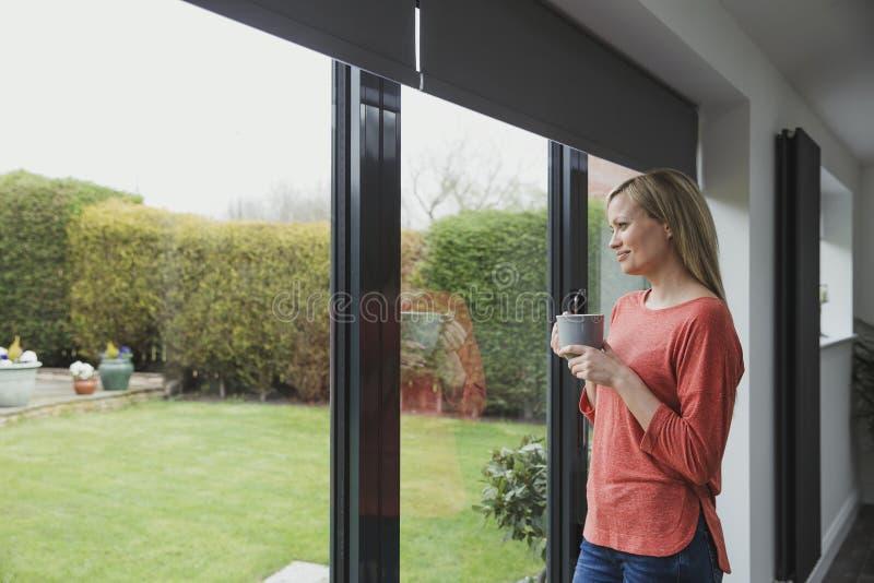 Donna premurosa alla finestra immagini stock