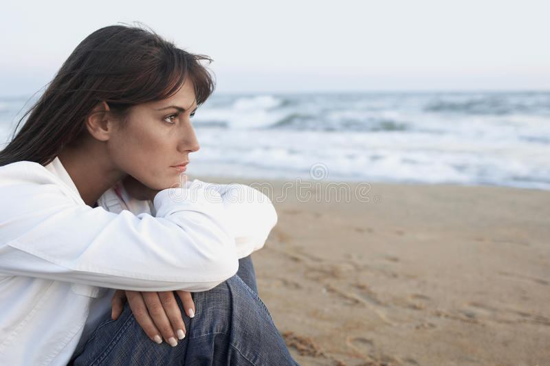 Donna premurosa che distoglie lo sguardo spiaggia fotografie stock