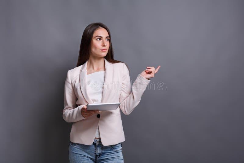 Donna premurosa con la compressa su fondo grigio immagine stock libera da diritti