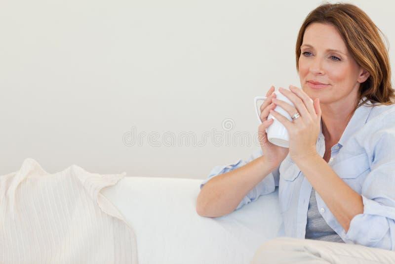 Donna premurosa con la tazza di caffè sul sofà fotografia stock