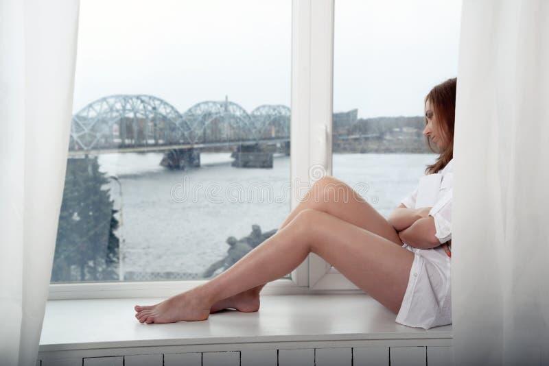 Donna premurosa con un libro che si siede vicino alla finestra fotografia stock libera da diritti