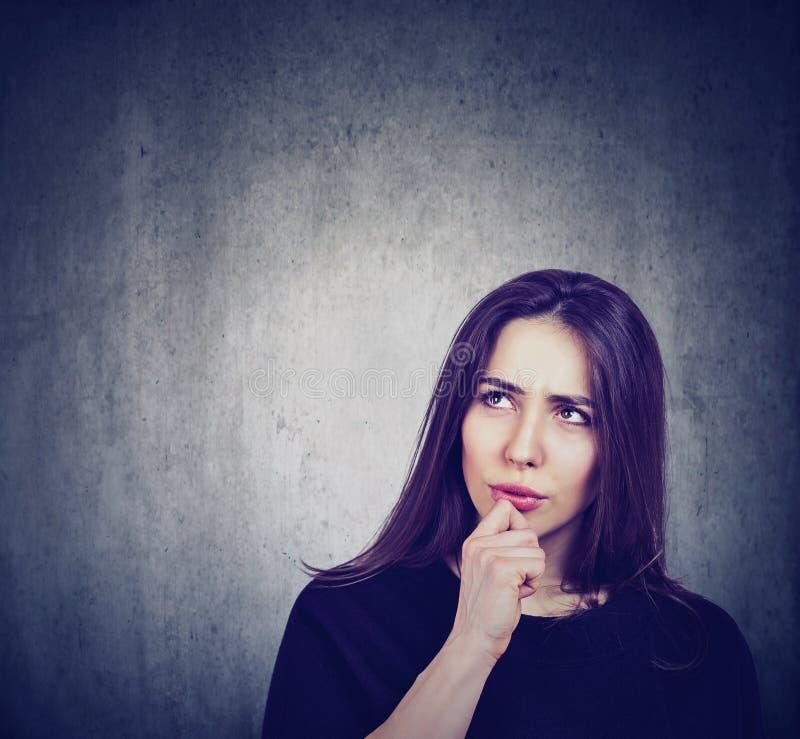 Donna premurosa pensierosa su un fondo della lavagna immagini stock