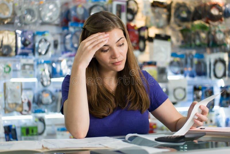 Donna preoccupata che controlla le fatture e le fatture nel negozio di computer immagini stock libere da diritti