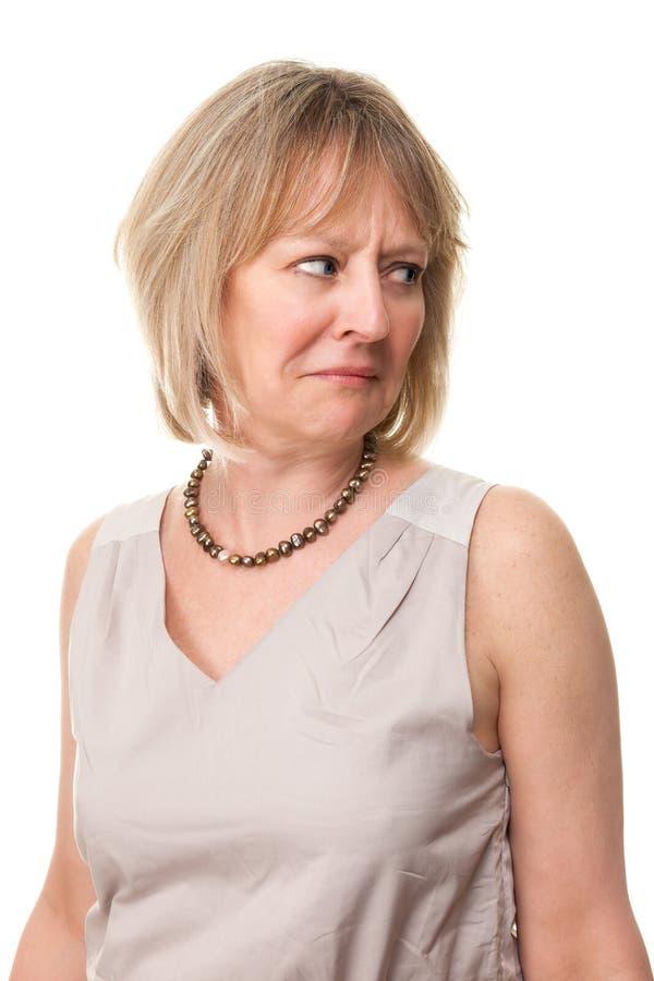 Donna preoccupata che osserva sopra la spalla fotografia stock