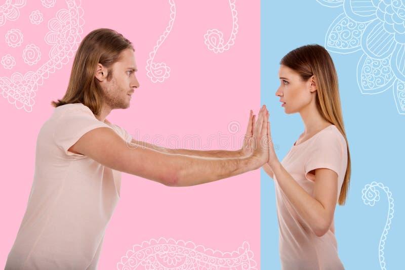 Donna preoccupata che sembra spaventata mentre il suo ragazzo che spinge le sue mani immagine stock libera da diritti