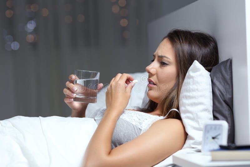 Donna preoccupata malata che protesta prendendo pillola nella notte fotografie stock