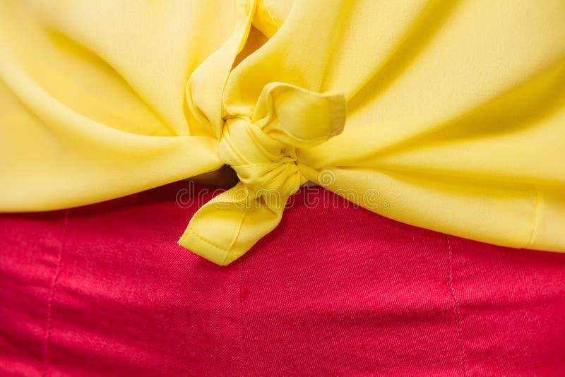 Donna in primo piano della camicia annodato giallo fotografie stock