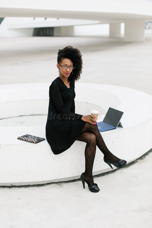 Donna professionale dei giovani capelli alla moda di afro facendo uso della compressa immagini stock