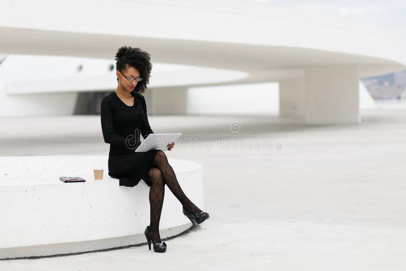 Donna professionale della giovane acconciatura alla moda di afro facendo uso della compressa immagine stock libera da diritti