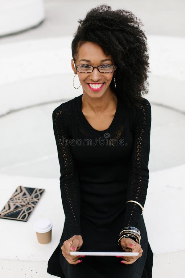 Donna professionale della giovane acconciatura alla moda di afro facendo uso della compressa immagini stock