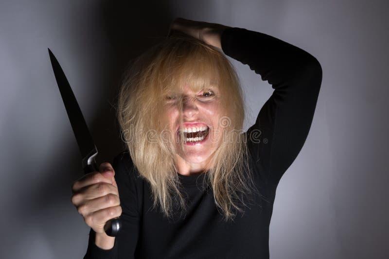 Donna psicotica con il coltello fotografie stock libere da diritti