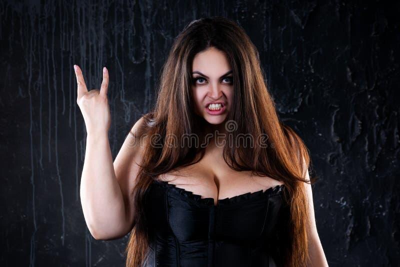 Donna punk arrabbiata che grida e che mostra i gesti della roccia su fondo nero immagini stock libere da diritti