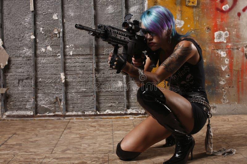 Donna punk che mira una pistola fotografia stock