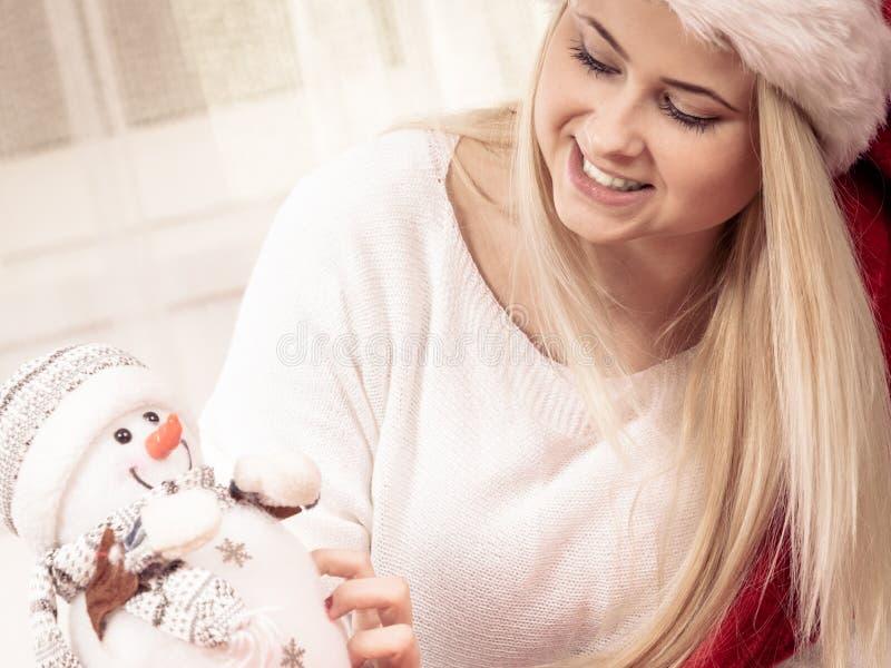 Donna in pupazzo di neve della tenuta del cappello del Babbo Natale immagini stock libere da diritti