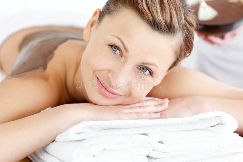 Donna radiante che si trova su una tabella di massaggio con fango immagine stock