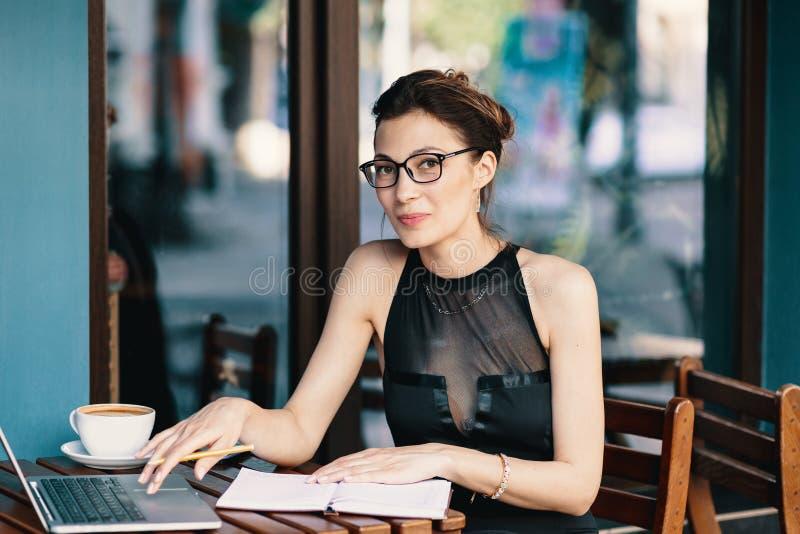 Donna raffinata di affari in vetri, sedentesi alla tavola nel funzionamento del caffè al computer portatile immagini stock libere da diritti