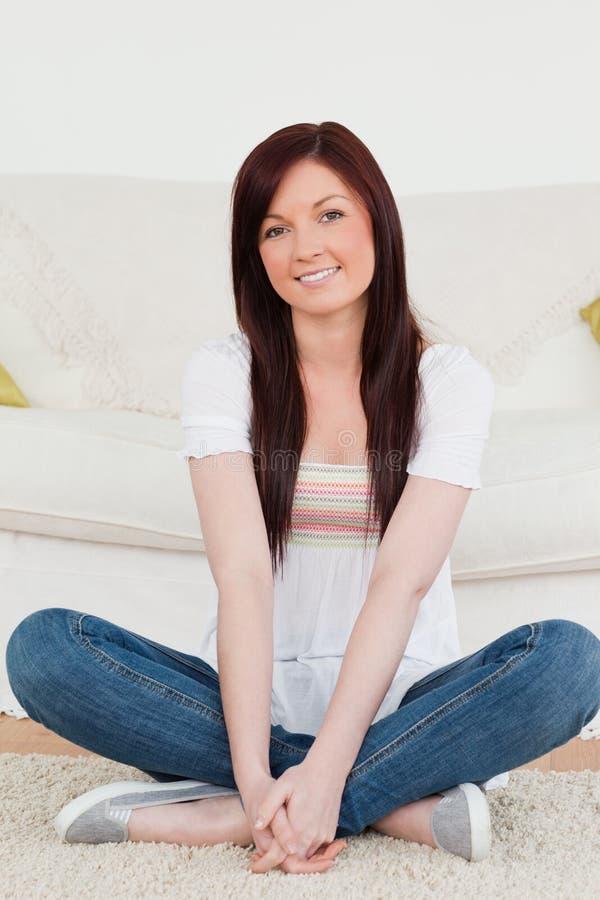 Donna red-haired sorridente che propone mentre sedendosi immagini stock