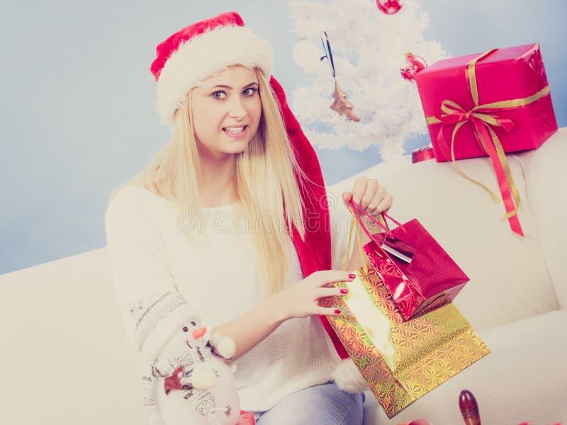 Donna in regali di natale dell'imballaggio del cappello di Santa fotografie stock libere da diritti