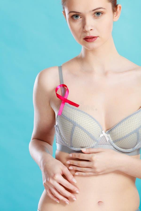 Donna in reggiseno con il nastro di consapevolezza del cancro al seno fotografie stock
