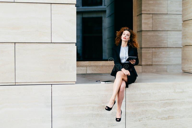 Donna riccia adorabile con lo sguardo sicuro, sedendosi da solo, dimostrante le sue gambe lunghe snelle, vestite in rivestimento  immagini stock libere da diritti