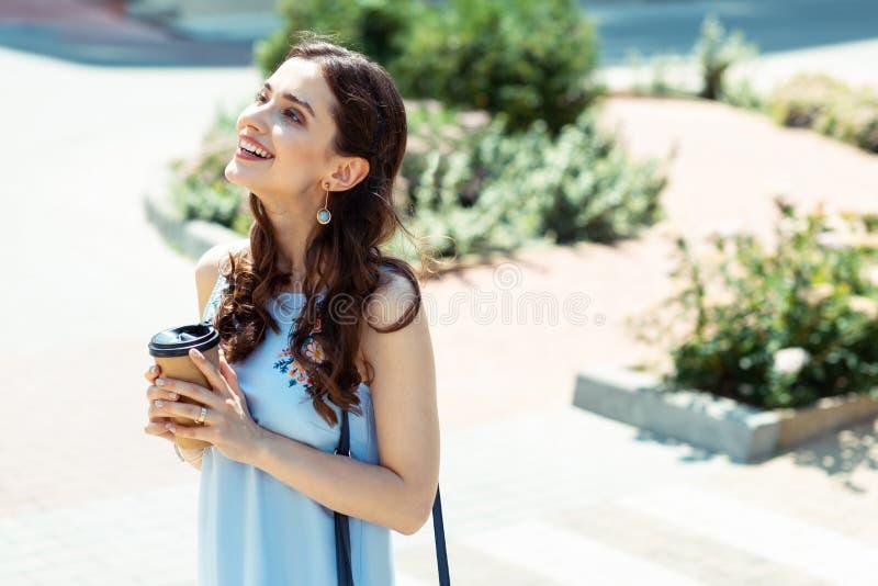 Donna riccia mora che ritiene l'esterno felice di tempo di spesa immagini stock