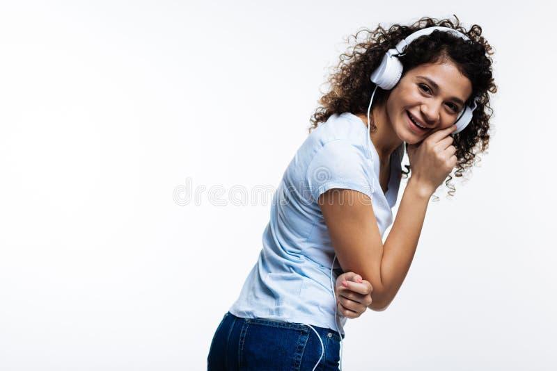 Donna riccio-dai capelli piacevole che ride mentre ascoltando la musica immagine stock