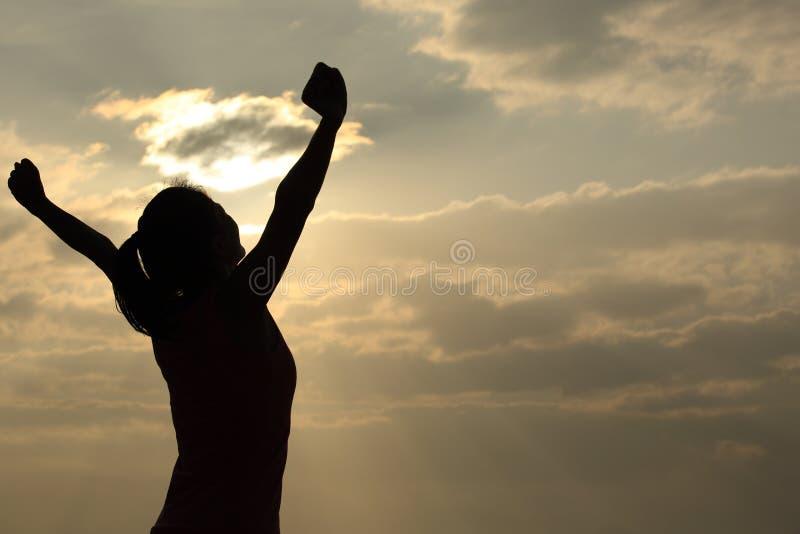Donna riconoscente a braccia aperte all'alba immagine stock